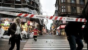 Police and emergency service workers cordon of an area near scaffolding on the famous Stroeget pedestrian street in central Copenhagen (28 October 2013)