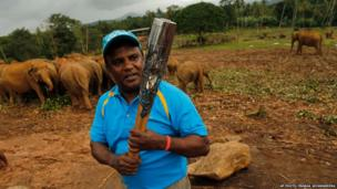 Sri Lankan athletic official holds the Queen's Baton during the Commonwealth baton relay at the Pinnawala elephant orphanage in the Kegalle District of Sri Lanka.