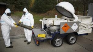 Employees in protective clothing unload a dummy grenade during a demonstration in a chemical weapons disposal facility in Munster, northern Germany