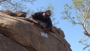 A game ranger removes one of several unlawfullly-placed memorial plaques attached to rocks in the Kruger National Park, South Africa