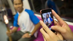 An athlete poses with the Queen's Baton while another takes a picture with a camera phone on the MRT metro system in Singapore.