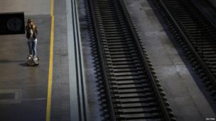 A woman waits for a train during a 24-hour nationwide train strike against the privatisation plans of railways by public companies in the Andalusian capital of Seville, southern Spain