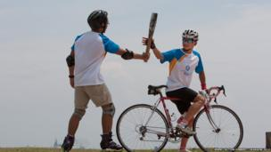 Rollerblader Lim Wu Kai hands over the Queen's Baton to cyclist Kenneth Kang in Singapore.