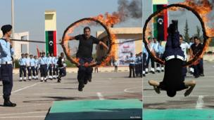 A new police officer jumps through a hoop of fire in Tripoli, Libya - Thursday 31 October 2013