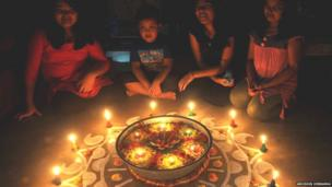 A family in India gathers around a circle of lit candles