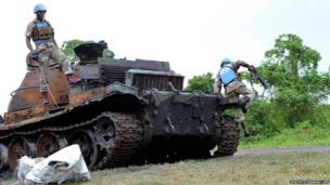 South African UN soldiers examine a burnt out tank