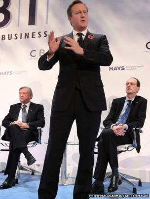 Prime Minister David Cameron (C) speaks at The Confederation of British Industry (CBI) annual conference watched by CBI President Sir Michael Rake (L) and Director General John Cridland