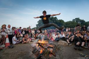 Man leaps across a fire at the Stone Circle at the Glastonbury Festival in Somerset