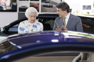 Queen Elizabeth II looks at a Jaguar motorcar at the Coronation Festival in the garden of Buckingham Palace