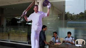 Security men sit beside a cut-out of Tendulkar at the entrance to Eden Gardens, the venue of the first Test match between India and West Indies, in Calcutta