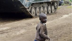 A child walks near a tank belonging to the Democratic Republic of Congo army in Rutshuru