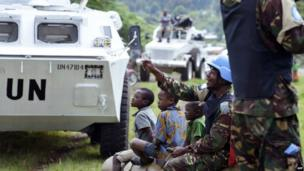UN troops from Tanzania seated near their vehicles with local children in the village of Kimbumba, in eastern Democratic Republic of Congo