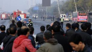 Commuters and residents gather near the site of multiple explosions outside a provincial office of China's ruling Communist Party in Taiyuan