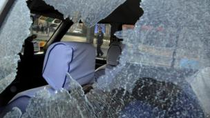 A Chinese police officer passes behind a vehicle damaged by explosions outside a provincial office of China's ruling Communist Party in Taiyuan