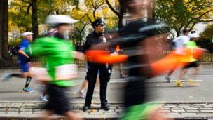A police officer stands guard while runners make their way through the borough of Manhattan during the New York City Marathon