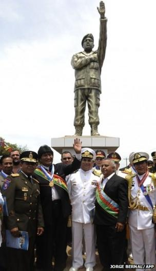 The President of Bolivia, Evo Morales waves next to military authorities after unveiling a statue paying homage to the late Venezuelan President Hugo Chavez
