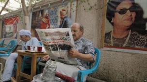 An Egyptian man reads the daily Al-Ahram newspaper fronted by pictures of the trial of Egypt's ousted President Mohammed Morsi at a coffee shop in Cairo on 5 November 2013