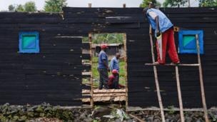 A builder works on the frame of a new house in Kibati, eastern Democratic Republic of Congo, on 6 November 2013