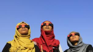 Women observe a solar eclipse during an event organized by the Sudanese Society for Astronomy and Space Science on the banks of the Nile river in Khartoum on 3 November 2013