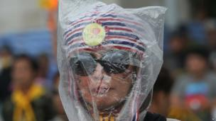 Anti-government protester wears a plastic bag to protect herself from tear gas during a rally against a political amnesty bill in Bangkok, Thailand