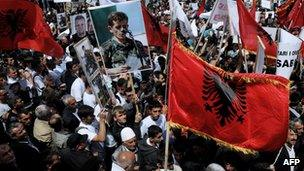 Kosovo Albanians wave Albanian flags and banners as they take part in a protest in Pristina on 27 May 2013
