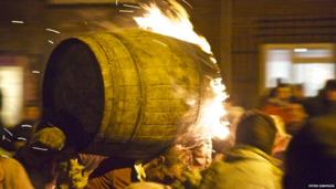 Flaming tar barrel being carried through the street. Photo: Peter Simpson