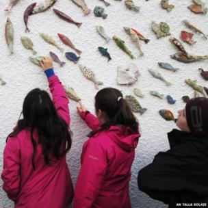 Children looking at fish sculpture