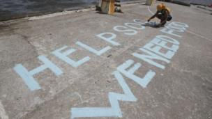 A survivor writes a message on their port to call for help at typhoon-ravaged Tacloban city, Leyte province, 11 November 2013