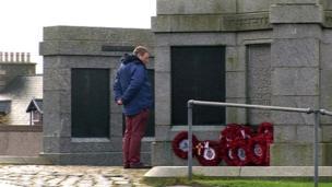 Man stands in front of a war memorial