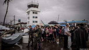 Typhoon victims wait to be evacuated at the airport in Tacloban