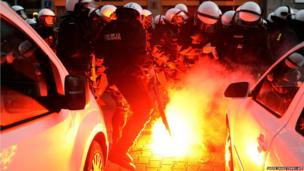 Police put out fires during clashes with protesters during Poland's national Independence Day in Warsaw
