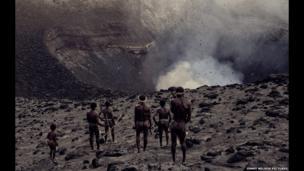 Ni-Vanuatus stand near an active volcano