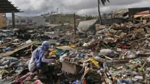 A survivor eats a banana which was found in garbage heap in typhoon-ravaged Tacloban city, central Philippines on 13 November 2013