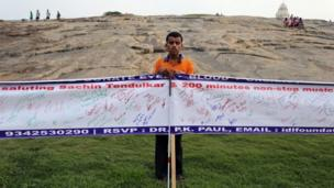 A member of a non-governmental organisation for the blind holds banners with messages for Sachin Tendulkar in Bangalore on 13 November 2013
