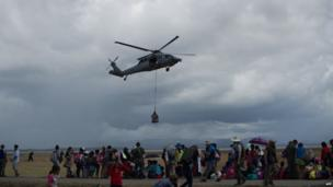 A US navy helicopter delivers relief supplies at Tacloban airport on 14 November 2013