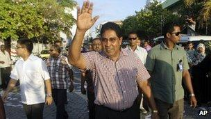 Presidential candidate Gasim Ibrahim, center, waves to supporters during an election campaign rally in Male