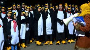 A group of people in penguin costume.