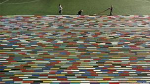 An enormously long scarf is laid out on a football pitch and loops back on itself a few dozen times.