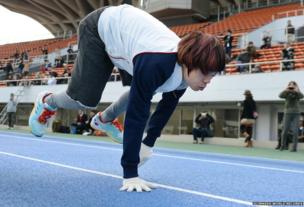 A man in sports wear is running on all fours. The photograph captures him in mid-aid with one hand still touching the floor.