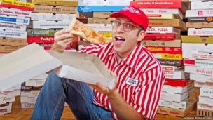A man sat amongst a collection of pizza boxes.