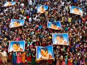 School children wave as they hold posters of Indian cricketer Sachin Tendulkar at an event to honour him inside a school in the southern Indian city of Chennai