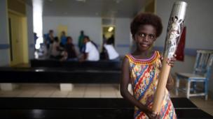 A young girl holds the Queen's Baton in the Outpatients Ward in Gizo Hospital in Gizo, Solomon Islands
