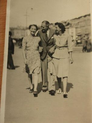 A man walks arm-in-arm with two women