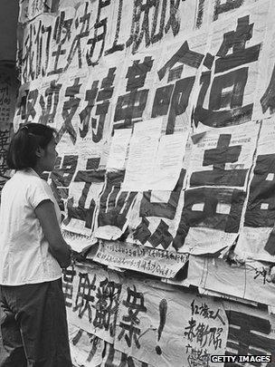 A Chinese girl reading propaganda posters in Guangzhou, 1966