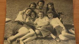 Seven women pose on grass