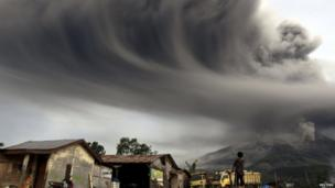 A woman looks on as Mount Sinabung spews ash, as pictured from Sibintun village in Karo district, Indonesia's north Sumatra province, 18 November 2013
