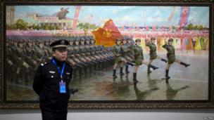 A security guard stands in front of an oil painting of North Korean female soldiers marching during their national parade, at an exhibition during the 13th Asian Arts Festival exhibition in Kunming, Yunnan province, China on 18 November 2013