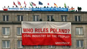 Polish Greenpeace activists climb on the roof of the Ministry of Economy in Warsaw, Poland, early on 18 November 2013
