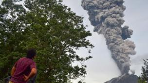 A man watches as Mount Sinabung volcano erupts in the Karo district on the north of Indonesia's Sumatra island on 18 November 2013