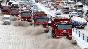 Snow clearing vehicles work on a road in Harbin, Heilongjiang province